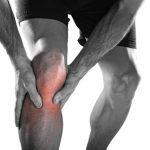 Sportler männlich, der sich das rechte Knie hält, weil er Schmerzen hat.