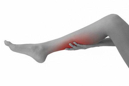 langes Frauenbein, dass durch eine Hand gehalten wird. Muskelkrampf und er Wade ist durch eine rote Stelle markiert