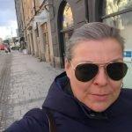 Frau mit Sonnenbrille und schmerzverzerrtem Gesicht