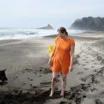 Frau Massage Strand barfuss mit orangenem Kleid